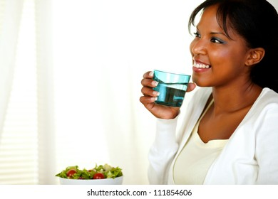 Portrait of a happy young adult woman with a sincere smile and drinking fresh water while looking to her right. With copyspace.