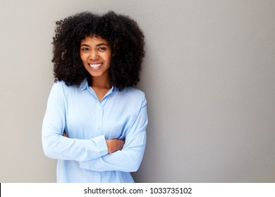 Portrait of happy young african american woman smiling against gray background with arms crossed