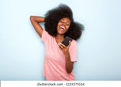 Portrait of happy young african american woman looking at cellphone text message