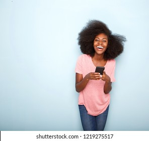 Portrait of happy young african american woman holding smart phone