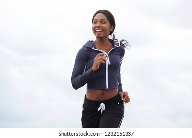 Portrait of happy young african american woman running outdoors