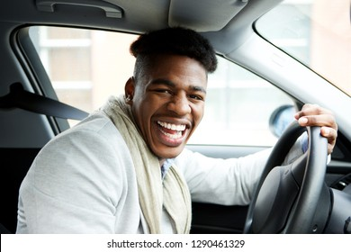 Portrait of happy young african american man sitting in car and laughing