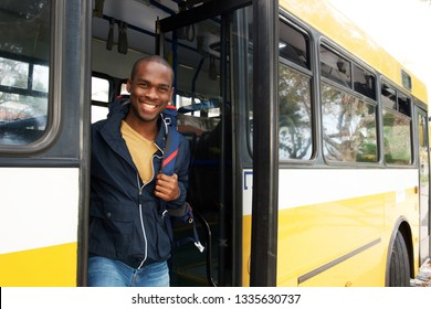 Portrait of happy young african american travel man with bag getting off bus