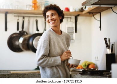 Portrait of happy young african american woman with cereal bowl in kitchen