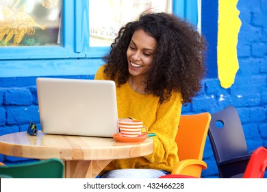 Portrait of happy young african american woman sitting at outdoor coffee shop and working on laptop