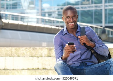 Portrait of happy young african american man sitting outdoors with mobile phone and smiling