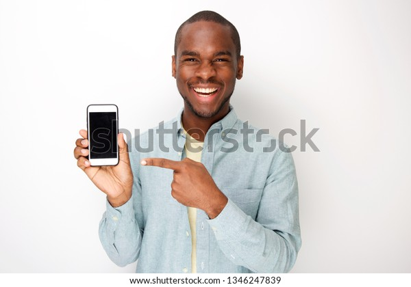 Portrait of happy young african american man holding mobile phone and pointing to screen
