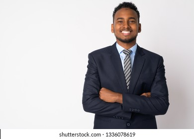 Portrait of happy young African businessman in suit smiling with arms crossed
