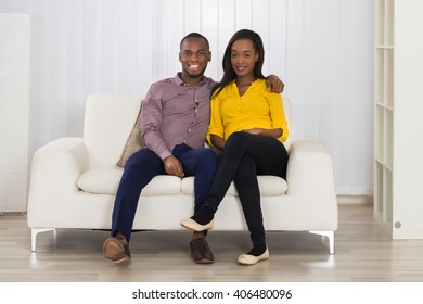 Portrait Of Happy Young African Couple Sitting On Sofa