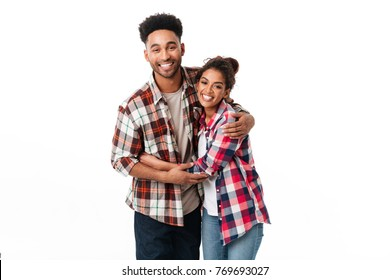 Portrait of a happy young african couple hugging while standing together and looking at camera isolated over white background