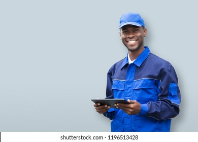 Portrait Of A Happy Young African Electrician Holding Mobile Phone