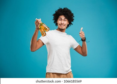 Portrait of a happy young african man holding beer bottles and showing thumbs up isolated over blue background