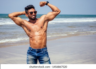 portrait of happy young african man on the beach.Handsome and confident Masculine hard fitness model male body bodybuilder with six pack.India trainer with perfect abs, shoulders,biceps, triceps,chest