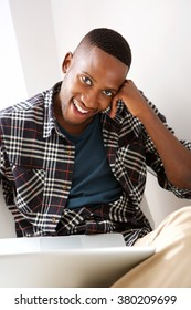 Portrait of happy young african man sitting with a laptop and looking at camera