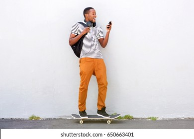 Portrait of happy young african man with skateboard looking at mobile phone