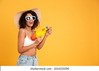Portrait of a happy young african woman dressed in summer clothes holding water pistol isolated over yellow background