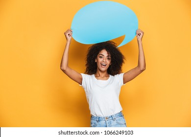 Portrait of a happy young african woman holding empty speech bubble isolated over yellow background