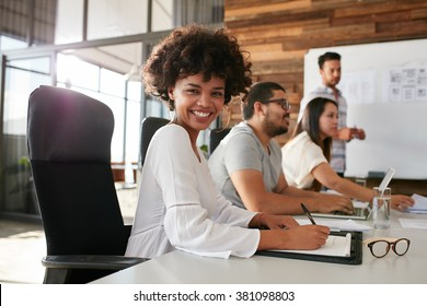 Portrait of happy young african woman sitting at a business presentation with colleagues in boardroom. Female designer with coworkers in conference room.