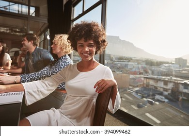 Portrait of happy young african woman sitting at a meeting with colleagues in background. Smiling creative professional looking at camera.