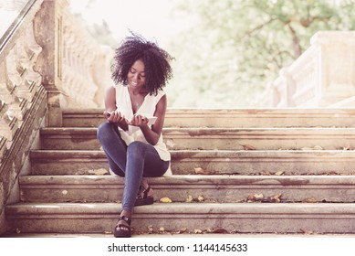 Portrait of happy young African-American female student wearing blouse and jeans sitting on stairs and reading copybook in autumn. Education and leisure concept