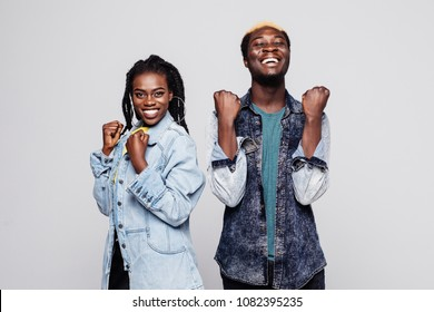 Portrait of a happy young afro american couple screaming and celebrating isolated over white