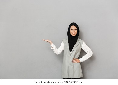 Portrait of a happy young arabian woman holding copy space on her palm away isolated over gray background