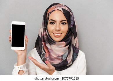 Portrait of a happy young arabian woman showing blank screen mobile phone isolated over gray background