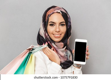 Portrait of a happy young arabian woman showing blank screen mobile phone while carrying shopping bags isolated over gray background