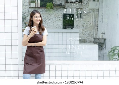 Portrait of a happy young Asian barista in apron holding hot coffee and standing in front of her small coffee shop.Startup Small Business Owner Concept. SME Business Concept.