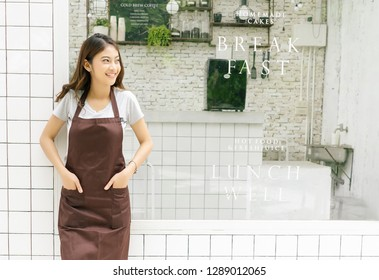 Portrait of a happy young Asian barista in apron smiling and looking away in front of her small coffee shop, waist up, copy space. Startup Small Business Owner Concept. SME Business Concept.