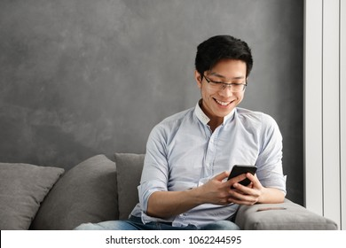 Portrait of a happy young asian man using mobile phone while sitting on a couch at home