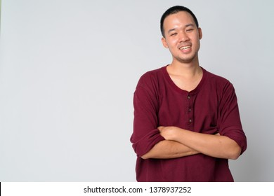 Portrait of happy young Asian man smiling with arms crossed