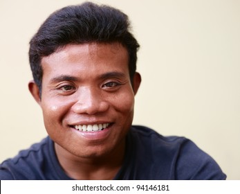 Portrait of happy young asian man smiling and looking at camera against yellow wall. Copy space