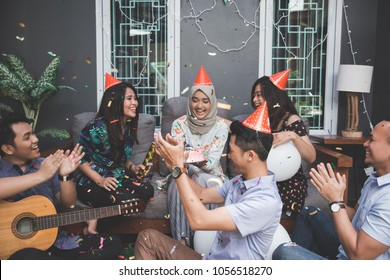 portrait of happy young asian people celebrating and singing birthday of their friends together at home