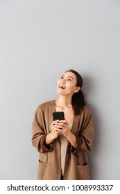 Portrait of a happy young asian woman holding mobile phone while standing and looking up at copy space over gray background
