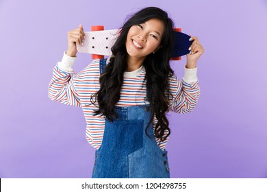 Portrait of a happy young asian woman isolated over violet background holding a skateboard on her shoulders