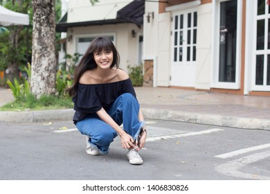 Portrait of happy young asian woman sitting and ties her sneaker