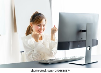 Portrait of happy young asian woman celebrating success with arms up in front of laptop at home.