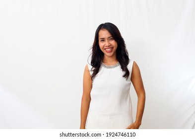 Portrait of happy young asian woman smiling against white wall