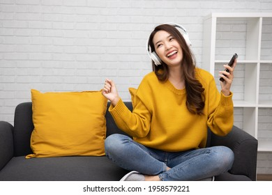 Portrait of a happy young Asian woman listening music with wireless headphones from music application on mobile smart phone in living room at condominium