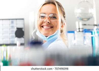 Portrait of happy young attractive smiling woman scientist with protective eyeglasses in the scientific chemical laboratory