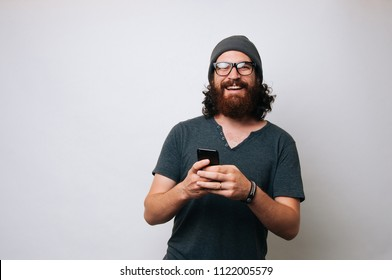 Portrait of a happy young bearded hipster man holding mobile phone while standing and looking at camera over white background