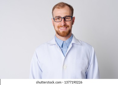 Portrait of happy young bearded man doctor smiling with eyeglasses