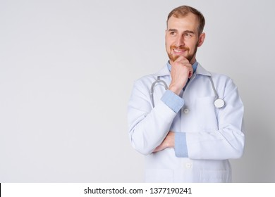 Portrait of happy young bearded man doctor thinking