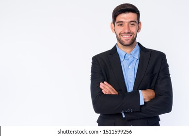 Portrait of happy young bearded Persian businessman smiling with arms crossed