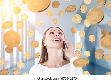 Portrait of a happy young and beautiful businesswoman talking on a smartphone and looking upwards. She is standing in an office. Bitcoins are falling around.