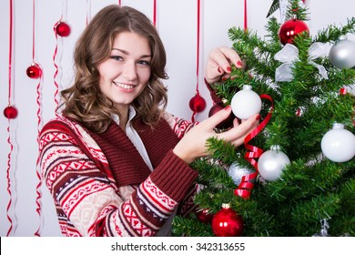 portrait of happy young beautiful woman decorating Christmas tree