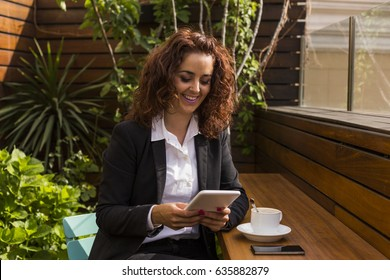 portrait of  a Happy young beautiful  woman smiling and using her tablet. Business woman on a terrace in the morning. Coffee time