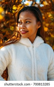Portrait of a happy young beautiful woman in autumn season in white woolen jacket outdoor with colorful autumn background.