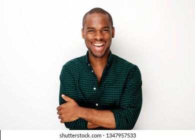 Portrait of happy young black guy smiling with arms crossed against isolated white background